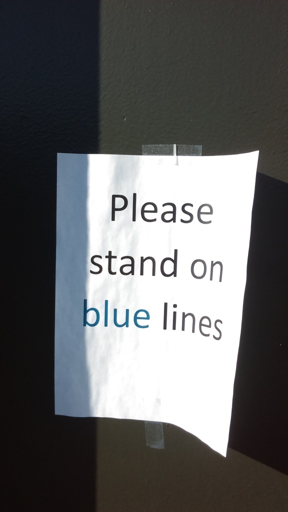 "A sign printed on white paper and taped to a pole reads, ""Please stand on blue lines,"" and the words are printed in black except the word blue, which is printed in blue."
