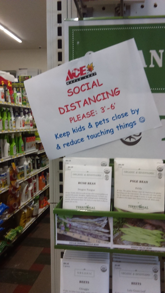 "On an end cap of an aisle with food seeds, a sign sits haphazardly above the seeds. The top of the sign shows the ACE Maple Leaf hardware store logo. Under that in red text and all caps, it reads, ""SOCIAL DISTANCING PLEASE: 3'-6'"" and below that is blue text that reads, ""Keep kids & pets close by & reduce touching things"" followed by a blue smiley face."