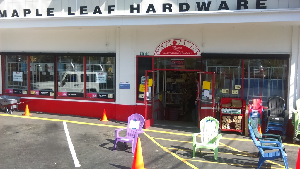 ACE Maple Leaf Hardware storefront. Both doors to the entrance are open. An employee stands just inside. A few feet outside of the door are two big plastic lawn chairs with signs on white paper taped to them with blue painter's tape. Between the chairs and a little further away from the doors is a traffic cone.