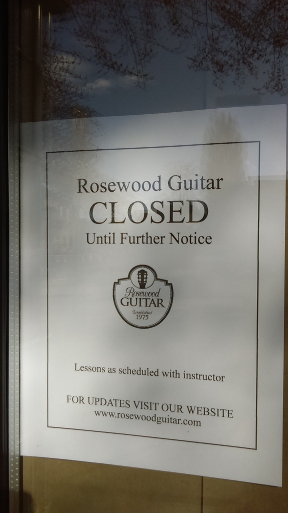 "March 23, 2020, Greenwood, Seattle. A sign on the door of Rosewood Guitar bears the name and crest of the store, and reads, ""CLOSED until further notice."" The bottom of the sign reads, ""Lessons as scheduled with instructor,"" and, ""FOR UPDATES VISIT OUR WEBSITE"" and has the web site www.rosewoodguitar.com listed below."