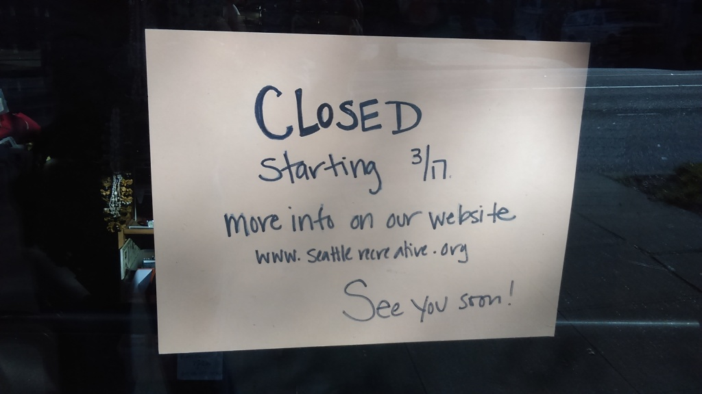 "March 23, 2020, Greenwood, Seattle. This is a closeup of the hand-written sign in the image to the left of the door of Seattle ReCreative. It reads, ""CLOSED starting 3/17. More info on our website www.seattlerecreative,org."" The bottom has an extra note that reads, ""See you soon!"""