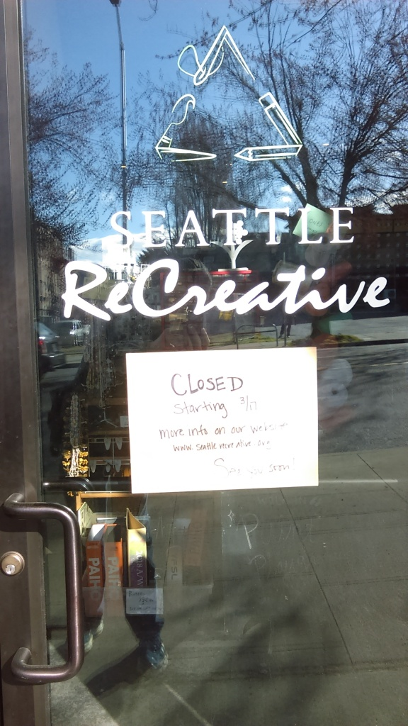March 23, 2020, Greenwood, Seattle. On the door of Seattle ReCreative is a sign that says the store is closed. A legible closeup of the sign is in the image to the right.