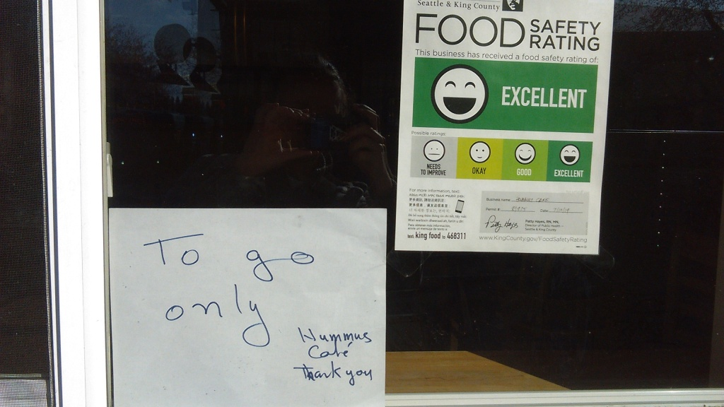 "March 23, 2020, Greenwood, Seattle. In the window of a local restaurant, a food safety rating sheet is displayed as required by law. This one has an ""excellent"" rating, which is the highest of four ratings. Next to the food safety rating sheet is a hand-written sign that says ""To go only"" and, in the bottom right corner, ""Hummus Cafe,"" and below that, ""Thank you."""