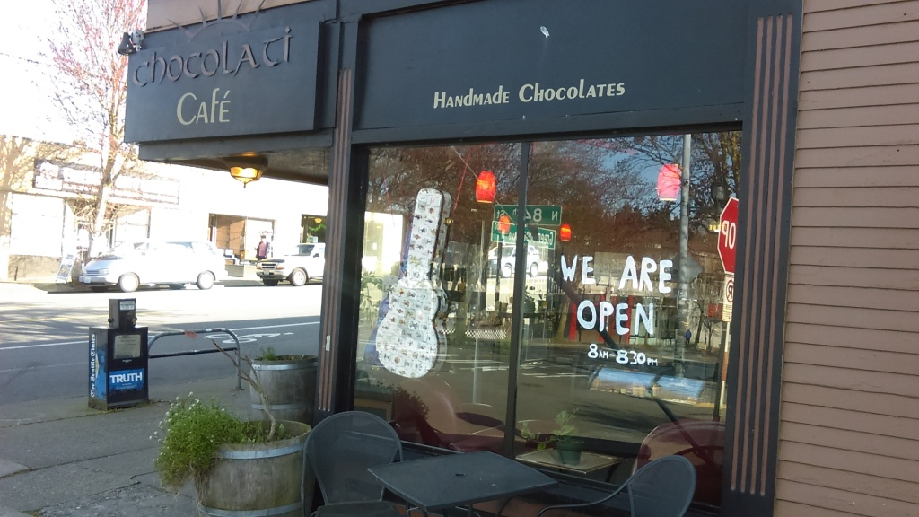 "March 23, 2020, Greenwood, Seattle. Big hand-written letters on the windows of Chocolati cafe read ""WE ARE OPEN."""