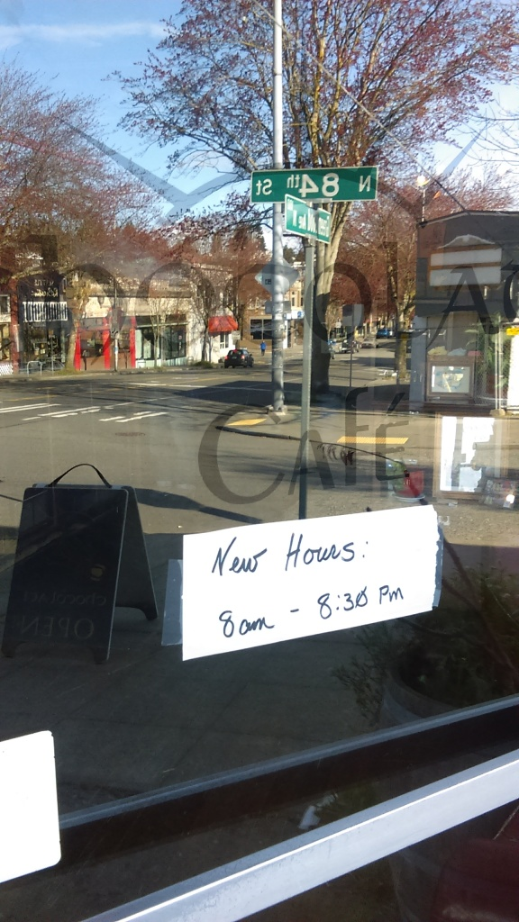"Aside from the street reflected in the window, this image shows a hand-written sign that reads ""New Hours: 8am - 8:30pm"" taped to the window under Chocolati Cafe's name."