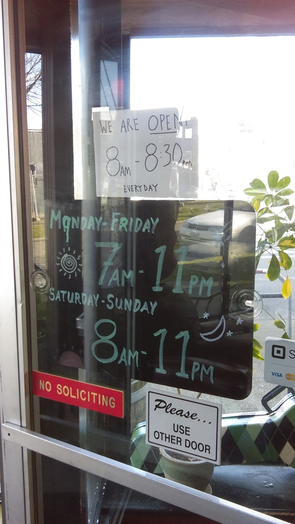 "March 23, 2020, Greenwood, Seattle. The door to Chocolati is plastered with signs such as ""NO SOLICITING"" and ""Please...USE OTHER DOOR."" A big black sign with neatly handwritten green chalk reads, ""MONDAY-FRIDAY 7AM-11PM,"" and ""SATURDAY-SUNDAY 8AM-11PM"" and is decorated with a sun and moon drawn in yellow. These are clearly the store's standard hours. A handwritten sign on white paper taped above it says, ""WE ARE OPEN 8:00AM - 8:30PM EVERYDAY."""