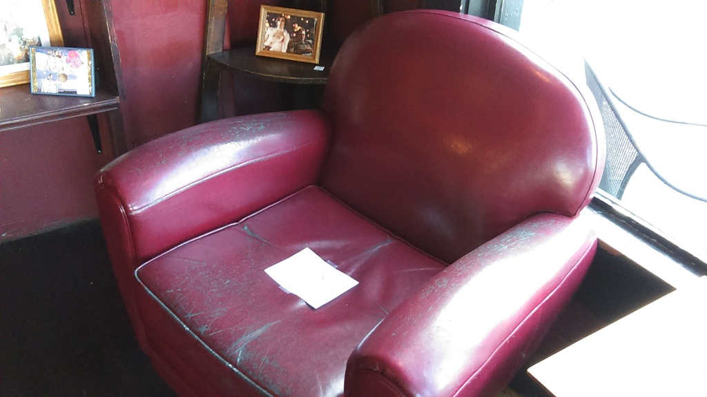 March 23, 2020, Greenwood, Seattle. One of two red leather chairs inside the barista bar area of Chocolati Cafe. It has a sign taped to the seat. The image below this one is a close up that shows what it says.